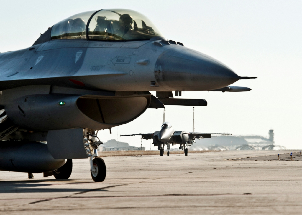 An F-16 Fighting Falcon waits for clearance as an F-15E Strike Eagle taxis in the distance Jan. 18, 2011, at Eglin Air Force Base Fla. Both aircraft belong to the 46th Test Wing. (U.S. Air Force photo/Samuel King Jr.)